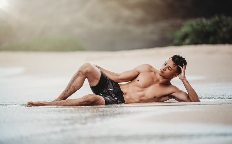 Orange County Portrait Photography, man laying on his side in the sand with a bathing suit