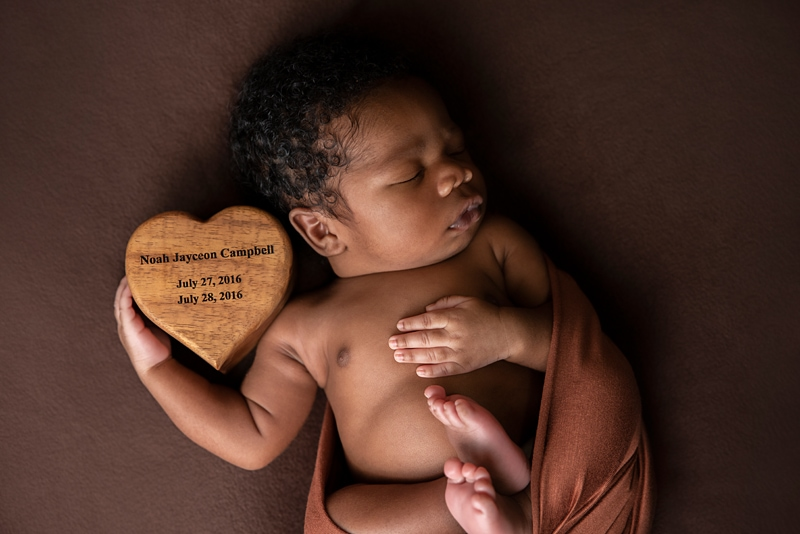 Orange County Newborn Photography, baby on brown background holding wooden heart box