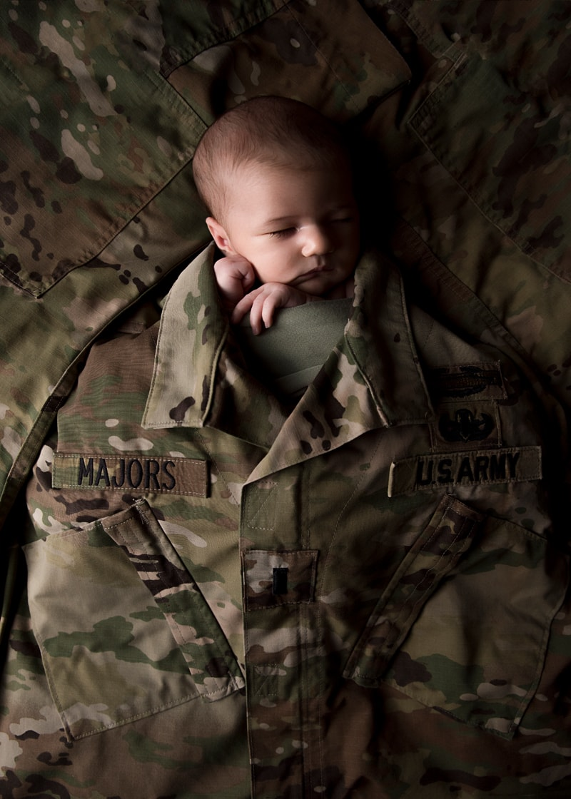 Orange County Newborn Photography, baby wrapped up in parent's military uniform