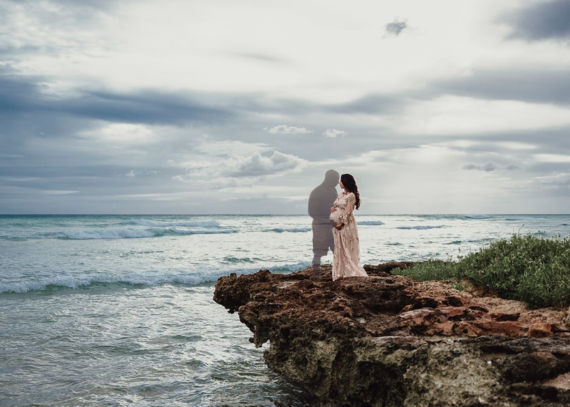 Orange County Maternity Photography, edited image of away father holding woman's belly on rocky cliff side of beach